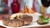 Porterhouse steak with herb fries and roasted garlic butter