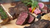 Dos porciones de bistec cocido sobre una tabla de madera maciza junto a otro bistec cocido