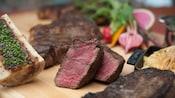 Deux tranches de steak cuit sur un bloc de boucher à côté d'un autre steak cuit