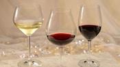Una copa de vino blanco cerca de una copa de vino tinto cerca de una copa de pinot noir
