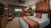 Une chambre au thème africain avec lit, canapé, table basse, commode, TV, table avec chaises et décoration murale