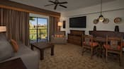 An African-themed living area with couch, coffee table, chair, lamps, dresser, TV, dining table and art