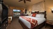 Cama king com cabeceira com cortina, travesseiros e almofada, castiçal de parede, terraço com cortina