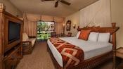 Cama king com cabeceira com cortina, TV no guarda-roupa de madeira, sofá-cama, terraço com cortina, mesa e cadeiras