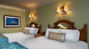 2 colonial-themed beds with headboards, wall sconces, side table with clock, crown molding, wall art