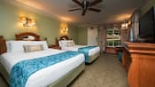 2 colonial-themed beds with headboards, wall sconces, ceiling fan, dresser, curtained window