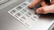 Gros plan sur les doigts d'un homme appuyant sur les touches d'un clavier d'un guichet automatique