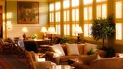 Mesa com sofás e cadeiras em uma sala de espera ensolarada ao lado de várias janelas