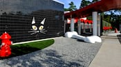 A shiny black exterior wall adorned with a large cat's face next to a gravel area with giant dog bone and a grass area with fire hydrant