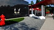 Uma parede externa em preto brilhante decorada com uma cara de gato grande, ao lado de uma área com cascalho com um osso de cachorro gigante e outra área coberta de grama com um hidrante.