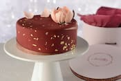 An Amorette's Patisserie signature cake on a pedestal next to its hat box packaging