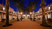Courtyard flanked by palm trees after dark