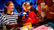 Un miembro del elenco ayuda a un niño con su proyecto de artes