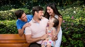 Surrounded by trees, a little girl sits on her dads lap while her mom and brother stand by the bench