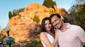 A happy couple pose together while surrounded by trees, flowers and a rocky mountain backdrop