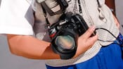 A camera with a large lens cradled in a Disney PhotoPass Photographer's arm