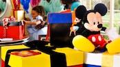 Caixas de presente com embalagem colorida e um grande Mickey de pelúcia sentado na tampa