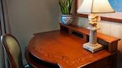 Un escritorio de madera con una planta en maceta, una lámpara de Mickey Mouse y una silla
