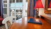 Un escritorio de madera, con una lámpara de Mickey Mouse, una guía para Huéspedes y una silla de madera blanca cerca de las puertas corredizas de vidrio del balcón