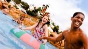Huéspedes en trajes de baño disfrutando del agua hasta la cintura en una piscina