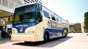 """Vista frontal de um ônibus azul e branco chamado """"Disney's Magical Express"""""""