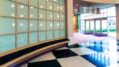 Black-and-white checkered flooring with a curved grid of frosted windows in a lobby