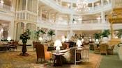 Áreas com poltronas de orelhas, poltronas de dois assentos e móveis de vime dentro do saguão do Disney's Grand Floridian Resort & Spa