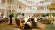 Áreas con butacas con respaldo, sillones y muebles de mimbre en el interior del vestíbulo de Disney's Grand Floridian Resort & Spa