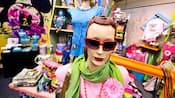 Mannequins in a retail store displaying sunglasses, scarves, necklaces and T-shirts