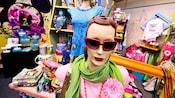 Manequins em uma loja de varejo exibindo óculos de sol, lenços, colares e camisetas