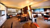 Lounge em um Hotel Resort Disney com mobiliário moderno, com acabamento em madeira e metal e uma televisão de tela plana