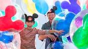 Pai e filho usam chapéus com orelhas do Mickey Mouse e riem cercados por balões do Mickey Mouse