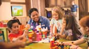 A Cast Member and kids play with a Lego Disney building set at a childrens activity center