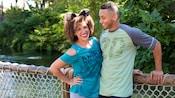 2Visitantes parados en un puente del Parque Temático Disney's Animal Kingdom, vestidos con ropa y accesorios del 20.ºaniversario