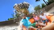 Un padre con su hijo y su hija son salpicados mientras dan un paseo familiar en balsa en Miss Adventure Falls