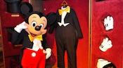 Mickey Mouse em frente a um armário repleto de roupas, incluindo seu traje a rigor e luvas brancas