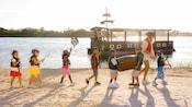 7 niños y una mujer disfrazados de piratas marchando en la playa