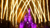 Cinderella Castle lit up in purple with fireworks blasting skyward