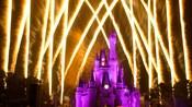 El Cinderella Castle iluminado en color púrpura con fuegos artificiales de fondo