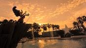 Estátua do Mickey Feiticeiro sobre a Fantasia Pool no Disney's All-Star Movies Resort ao anoitecer