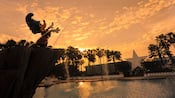 Statue of Sorcerer Mickey standing over Fantasia Pool at Disney's All-Star Movies Resort at sunset