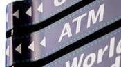 """Placas direcionais que lembram um filme, uma com setas e as letras """"ATM"""""""