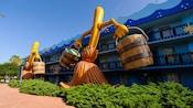 2 versiones gigantes de las escobas bailarinas con baldes en las manos de Fantasía de Disney adornan el costado de Disney's All-Star Movies Resort