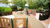 Un patio de juegos con arena, con un aparato gigante para trepar, un tobogán, redes y barras para trepar