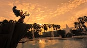 Silhouette against a sunset sky of Sorcerer Mickey Fountain at Fantasia Pool at Disney's All-Star Movies Resort