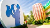 Circular structure with a saxophone player's silhouette across a path from a giant drum adorning the side of Disney's All-Star Music Resort