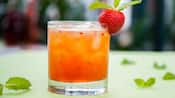 A drink in a glass garnished with a strawberry and a sprig of mint