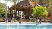 Children play in a pool while adults walk and lounge near a bar with a sign that reads Maji