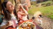Uma família sorridente saboreia uma refeição à mesa de um restaurante enquanto a filha brinca com um binóculo