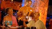 Un couple rit tandis qu'il boit à côté de nourriture et 2membres du personnel de cuisine